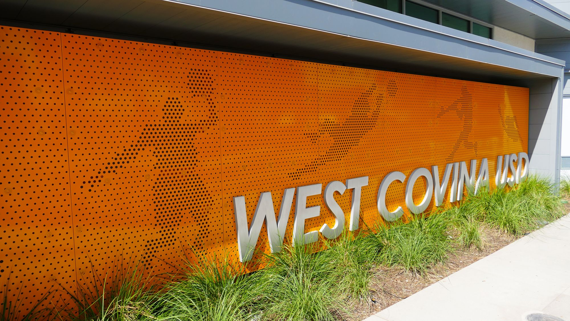 Entryway featuring custom Perforated Metal panels that represent campus activities